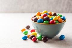 Kolorowi czekoladowi guziki w pucharze na szarość drylują tło Fotografia Stock