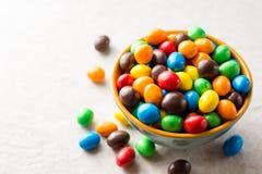 Kolorowi czekoladowi guziki w pucharze na szarość drylują tło Obraz Royalty Free