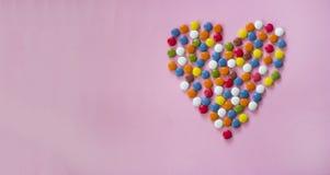 Kolorowi dragees tworzy serce Zdjęcia Royalty Free