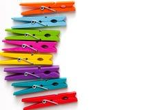 Kolorowi drewniani clothespins na białym tle z odbitkowym space/ fotografia stock