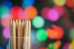 Kolorowi drewniani ołówki na kolorowym tle Zdjęcia Stock