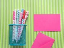 Kolorowi dziewczęcy pióra na zielonym tle z kartą Obraz Stock