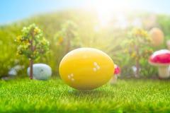 Kolorowi Easter jajka i jeden duży żółty Easter jajko na wiosny zielonej trawie Fotografia Royalty Free