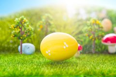 Kolorowi Easter jajka i jeden duży żółty Easter jajko na wiosny zielonej trawie Zdjęcia Royalty Free