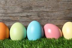 Kolorowi farbujący Wielkanocni jajka na zielonej trawie przeciw drewnianemu tłu obraz royalty free