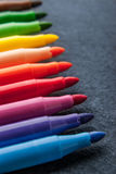 Kolorowi filc pióra na zmroku drylują tła vertical Fotografia Stock