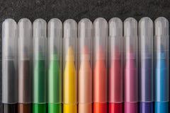 Kolorowi filc pióra na zmroku drylują tło Obrazy Royalty Free