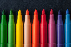 Kolorowi filc pióra na zmroku drylują tło horyzontalnego Obrazy Royalty Free