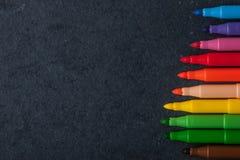 Kolorowi filc pióra na zmroku drylują tło odgórnego widok Zdjęcie Stock