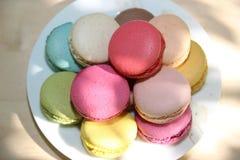 Kolorowi francuscy macaroons na białym talerzu Kolorowi francuscy macaroons z kawą na natury tle Fotografia Royalty Free