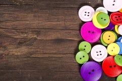 Kolorowi guziki na drewnianym tle. zdjęcia stock