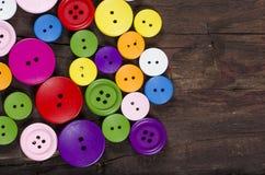 Kolorowi guziki na drewnianym tle obrazy stock