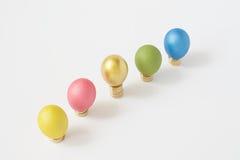 Kolorowi jajka stawiający na stosie złocistych monet bielu tło Obraz Stock