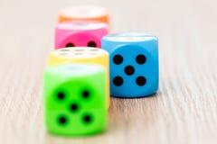 Kolorowi kostka do gry na drewnianej powierzchni Zdjęcia Stock