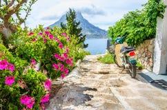 Kolorowi kwiaty i hulajnoga parkujący na drogowym Grecja Obrazy Stock