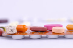 Kolorowi leki dalej nakrywają upakowanego lekarstwo Zdjęcia Stock
