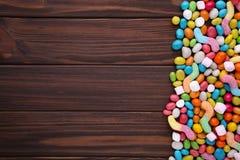 Kolorowi lizaki i różny barwiony round cukierek na brązu drewnianym tle zdjęcia stock
