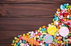 Kolorowi lizaki i różny barwiony round cukierek na brązu tle obraz royalty free