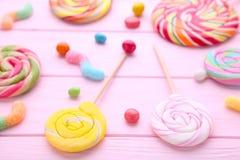 Kolorowi lizaki i różny barwiony round cukierek na różowym drewnianym tle zdjęcie royalty free