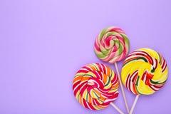 Kolorowi lizaki na purpurowym tle, cukierki cukierku pojęcie obrazy royalty free