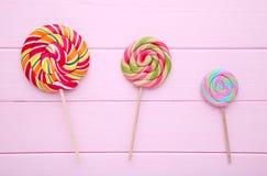 Kolorowi lizaki na różowym drewnianym tle, cukierki obrazy royalty free
