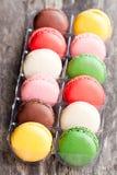 Kolorowi macarons na nieociosanym drewnianym backrgound Zdjęcie Royalty Free