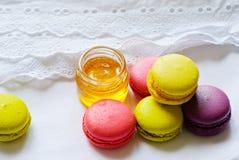 Kolorowi macaroons i słój miód Obrazy Stock