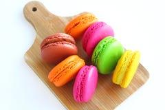 Kolorowi macaroons na tnącej desce Zdjęcia Royalty Free