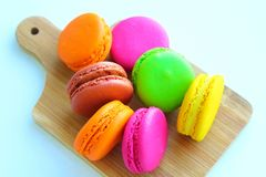 Kolorowi macaroons na tnącej desce Zdjęcia Stock