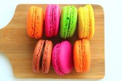 Kolorowi macaroons na tnącej desce Zdjęcie Stock