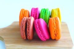 Kolorowi macaroons na tnącej desce Fotografia Stock