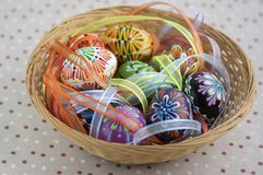Kolorowi malujący Wielkanocni jajka w brązu łozinowym koszu zakrywającym z kolorowymi faborkami, tradycyjny wielkanocy życie wcią zdjęcie royalty free
