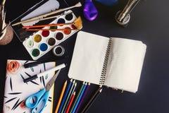Kolorowi ołówek farb muśnięć nożyce i notatnik na chalkb fotografia royalty free