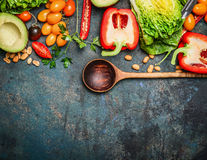 Kolorowi organicznie warzywa z drewnianą łyżką, składnikami dla sałatki lub plombowaniem na nieociosanym drewnianym tle, odgórny  Zdjęcia Stock