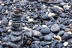 Kolorowi otoczaki dotyka fala przy piękną rockową wyspą Fotografia Stock