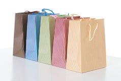 Kolorowi pasiaści torba na zakupy układali z rzędu, przedmiot odizolowywający na bielu Obraz Stock