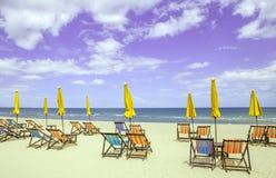 Kolorowi plażowi krzesła i zamknięci słońce parasole na pięknym beac Obrazy Stock