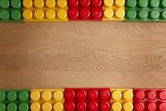 Kolorowi plastikowi budowa bloki na drewnianym tle jak ramę Mieszkanie nieatutowy Odgórny widok Obraz Royalty Free