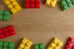 Kolorowi plastikowi budowa bloki na drewnianym tle jak zabawki obramiają internu z kopii przestrzenią dla teksta Mieszkanie nieat Zdjęcia Stock