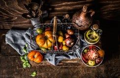 Kolorowi pomidory w zbierać kosz na ciemnym drewnianym stołowym tle fotografia stock