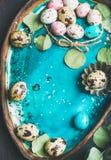 Kolorowi przepiórek jajka, kwiaty, liście dla wielkanocy nad błękitną tacą Obraz Stock