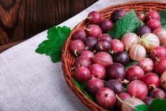 Kolorowi różowi agresty pełno odżywcze witaminy w koszu na szarej tkaninie na drewnianym tle i _ Zdjęcia Stock