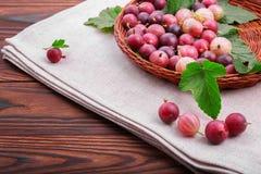 Kolorowi różowi agresty pełno odżywcze witaminy w koszu na szarej tkaninie na drewnianym tle i _ Obrazy Stock