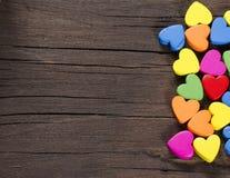 Kolorowi serca na drewnianym tle. obraz stock
