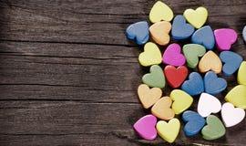 Kolorowi serca na drewnianym tle. zdjęcia royalty free