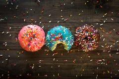 Kolorowi smakowici b?yskaj?cy donuts na drewnianym tle fotografia royalty free