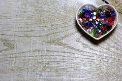 Kolorowi szklanych koralików serca na drewnianym tle Fotografia Stock