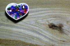 Kolorowi szklanych koralików serca na drewnianym tle Zdjęcie Stock