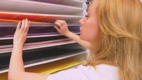 Kolorowi sztuka papiery na półce dla sprzedaży w materiały sklepie kobieta wybiera prześcieradła barwiony papier w sklepie zbiory wideo