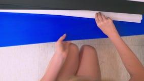 Kolorowi sztuka papiery na półce dla sprzedaży w materiały sklepie kobieta wybiera prześcieradła barwiony papier w sklepie zbiory